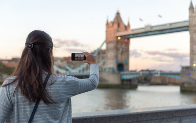 Junge Touristin macht Fotos von der Tower Bridge bei Sonnenuntergang