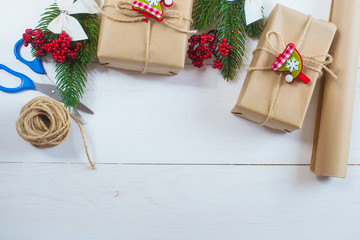 Christmas gift and a sprig of pine needles on a white wooden background