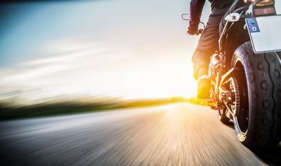 Motorrad fährt auf freier Landstrasse in den Sonnenuntergang Wall mural