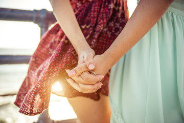 Two girls holding each other hands. Ladies couple on the beach