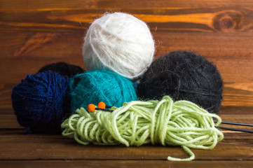 Several multi-colored balls of knitting yarn with spokes. On a wooden background.