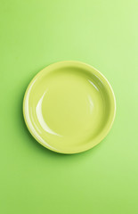 Green plate on green background,above view.Useful as a food back