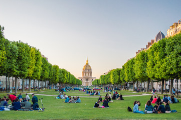 The National Residence of the Invalids and people sitting on a grass in Paris, France
