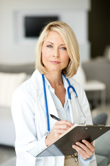Blond Woman Doctor Taking Notes in Office with Clipboard