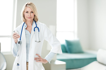 Blond Woman Doctor in Office with Mobile Phone