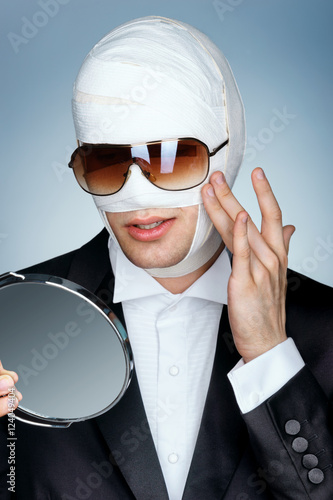 Glamorous Man In Sunglasses Looking In The Mirror Touching His New