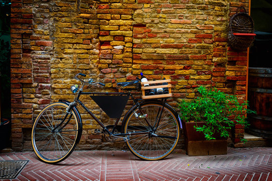 Old bike with wooden box on the street in San Gimignano, Italy