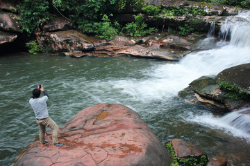 the man take a picture at beautiful waterfall