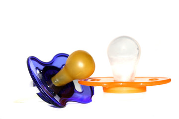 Two baby pacifiers on a white background