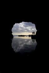 Silhouette Of Surfer On Beach Through Cave, Muriwai Beach, North Island, New Zealand