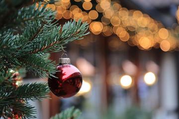 Christmas street decorations - red ball, fir and bokeh lights  Fotomurales
