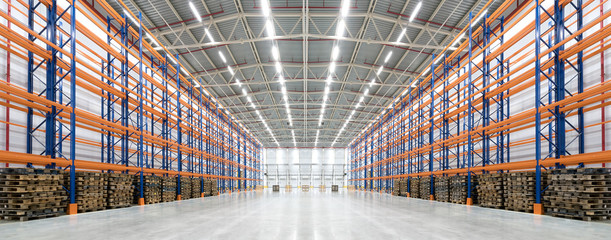 Panorama of an empty huge distribution warehouse with high shelves and pallets