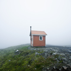 A Small Structure In The Middle Of A Wide Open Space Surrounded By Fog; Iceland
