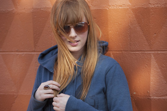 Portrait Of A Young Woman Wearing Sunglasses And Standing Against A Wall; Edmonton, Alberta, Canada