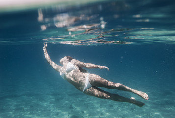 A Woman Swimming Underwater Wearing A Two Piece Bathing Suit; Tarifa, Cadiz, Andalusia, Spain
