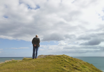 Man Standing Alone On A Hill Staring At The Ocean At Inchydoney Beach Near Clonakilty; County Cork, Ireland