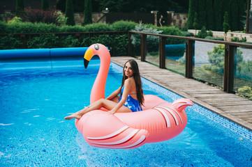 29b4b05602c99 Beautiful pregnant woman, wearing swimsuit, lying on a pink flamingo ...