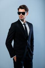 Portrait of brutal handsome man in black glasses holding hands i