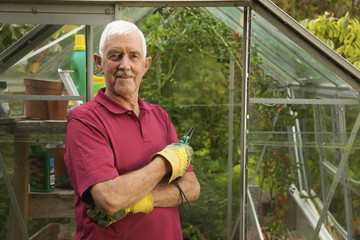 A Man Standing Outside A Greenhouse Wearing Gardening Gloves; Naas, County Kildare, Ireland