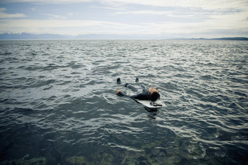 A Surfer Lays On His Back On His Surfboard In The Water; Victoria, British Columbia, Canada