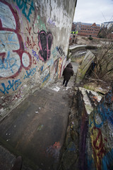 A Person Walks In An Alleyway Beside A Building And Wall Covered In Graffiti; Newcastle, Northumberland, England
