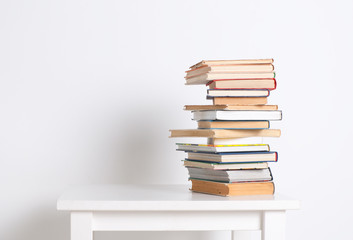 Stack of hardback books on the white table. Search for relevant and necessary information.