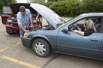 A Man Helps Boost The Car Battery Of A Woman's Car In A Parking Lot; Edmonton, Alberta, Canada
