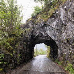 A Wet Road Leading Through A Tunnel In A Rock Cliff; Bergen, Norway