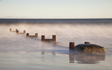 Wooden Posts And Boulders Immersed In Water At The Coast; Northumberland, England