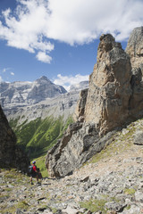 Male Hiker In The Distance On Rocky Trail With Large Sentinels And Mountains In The Background With Blue Sky And Clouds; Alberta, Canada