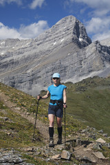 Female Hiker With Hiking Poles On A Mountain Trail With Mountain Peak In The Background And Blue Sky With Clouds; Alberta, Canada