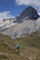 Female Hiker In The Distance On A Mountain Trail With Mountain Peak In The Background And Blue Sky With Clouds; Alberta, Canada