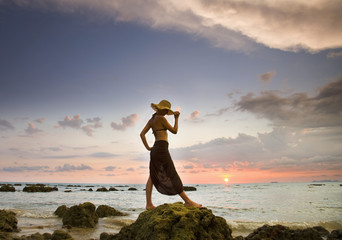 A Woman Wearing A Hat And Sarong Stands On The Beach Of A Tropical Island At Sunset; Koh Lanta, Krabi Province, Thailand