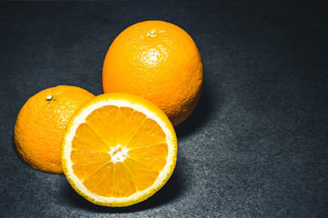 Orange cut into half. Fruit section on black surface.