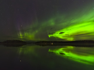 Beautiful aurora borealis over the lake with water reflection. Natural background.