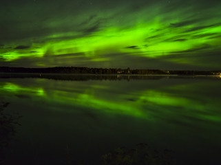 Beautiful green northern lights over lake water. Natural poster.