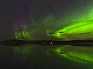 Beautiful green and purple northern lights with water reflection. Natural poster.