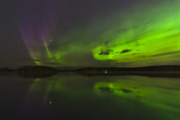 Beautiful green and purple northern lights over a lake. Natural poster.