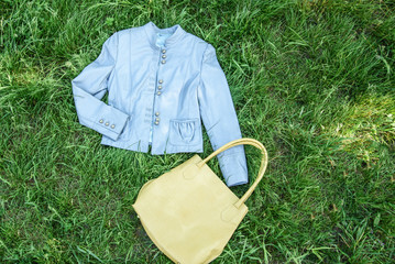Fotobehang a blue leather jacket on green grass with yellow bag