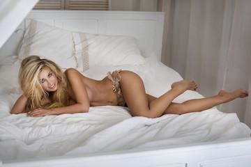 Sensual blonde woman in bed.