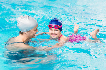 Smiling little girl, learning swimming with instructor