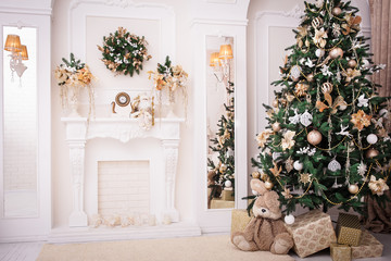 Christmas background. New Year interior design. Decorated tree near fireplace in great white living room.