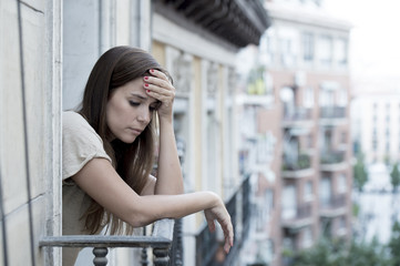 young sad beautiful woman suffering depression looking worried and wasted on home balcony