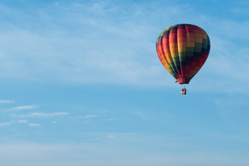 This is a photo of a beautiful hot air balloon slowly sailing through a calm blue sky.