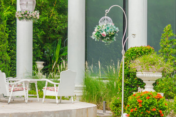 Relaxing space in cozy garden./ White tableset and flower pot on relaxing space in cozy garden on summer.