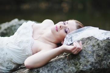 Bride lying on river rocks
