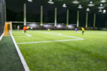 defocused of people playing soccer in the Artificial Turf soccer field