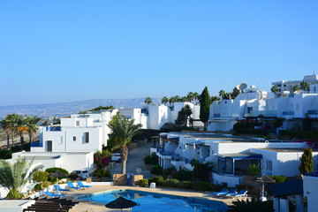 Classical Greek architectureat dawn: white and blue dotted buildings, palm trees, swimming pool