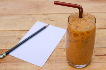 Iced coffee with  paper and pencil on Wooden background.