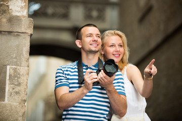 Positive man and woman tourists photographing in city